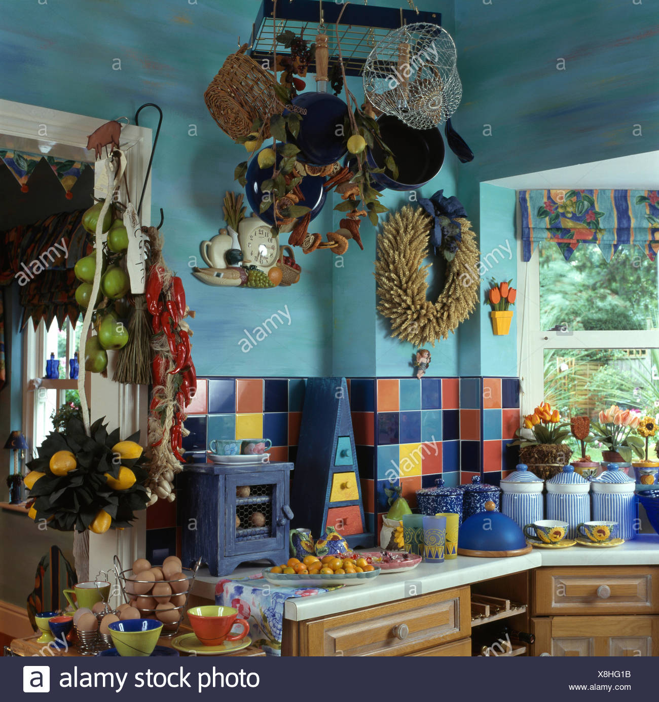 Colorful tiles on splash back in a small blue cluttered nineties ...