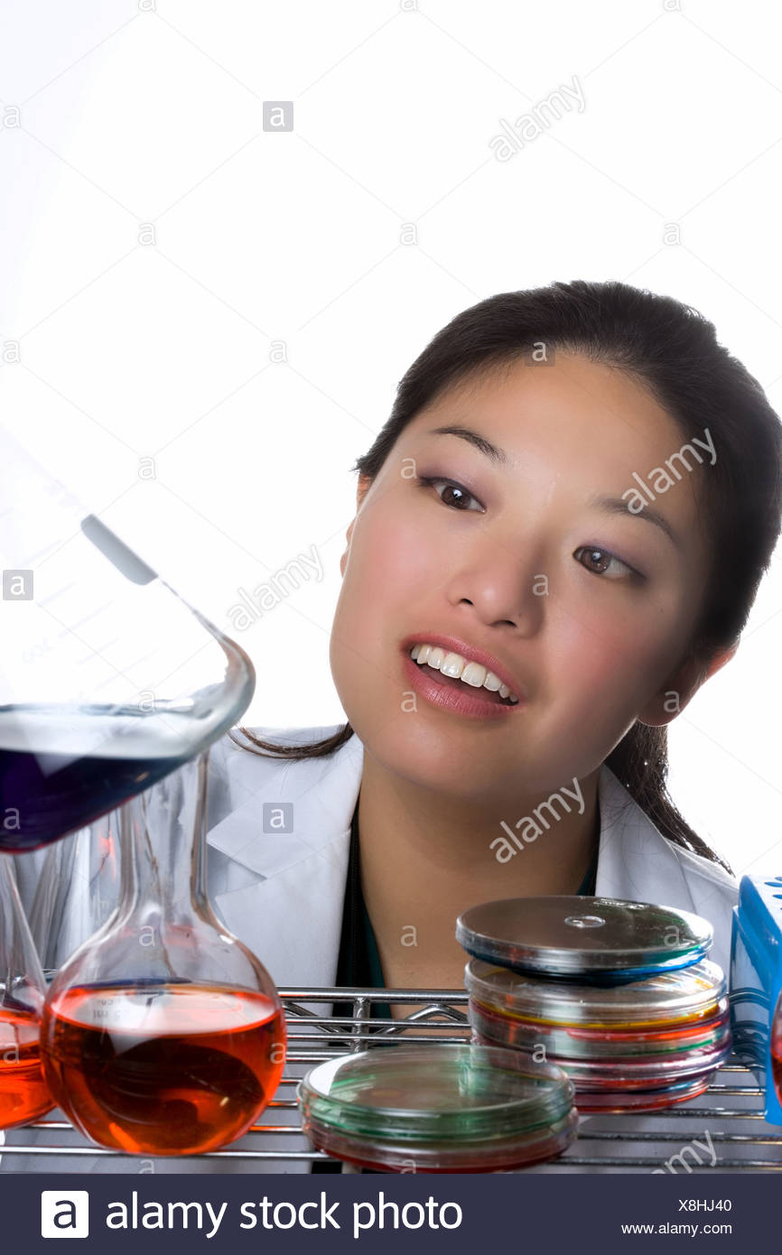 Woman mixing solutions in lab. - Stock Image