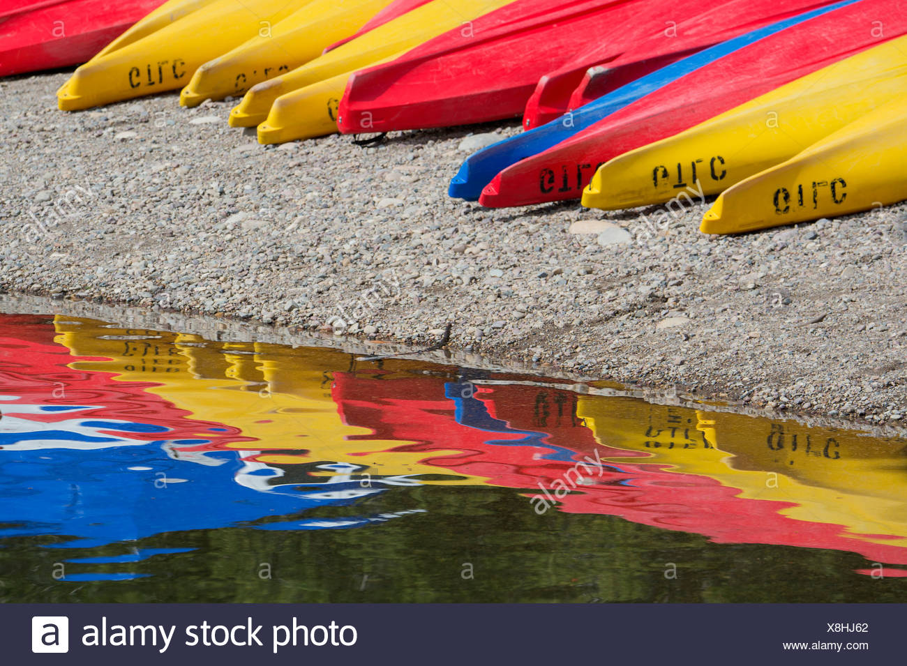 Kayaks for hire, laid out on the shores of Colter Bay at Jackson lake in the Grand Teton National Park. - Stock Image
