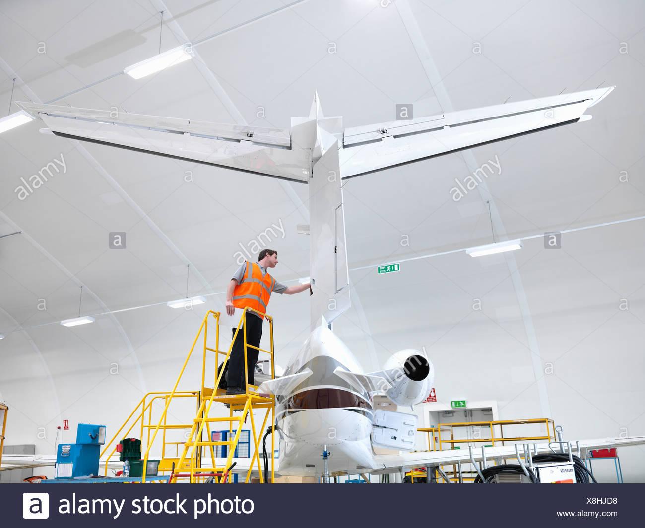 Engineer inspecting jet aircraft - Stock Image