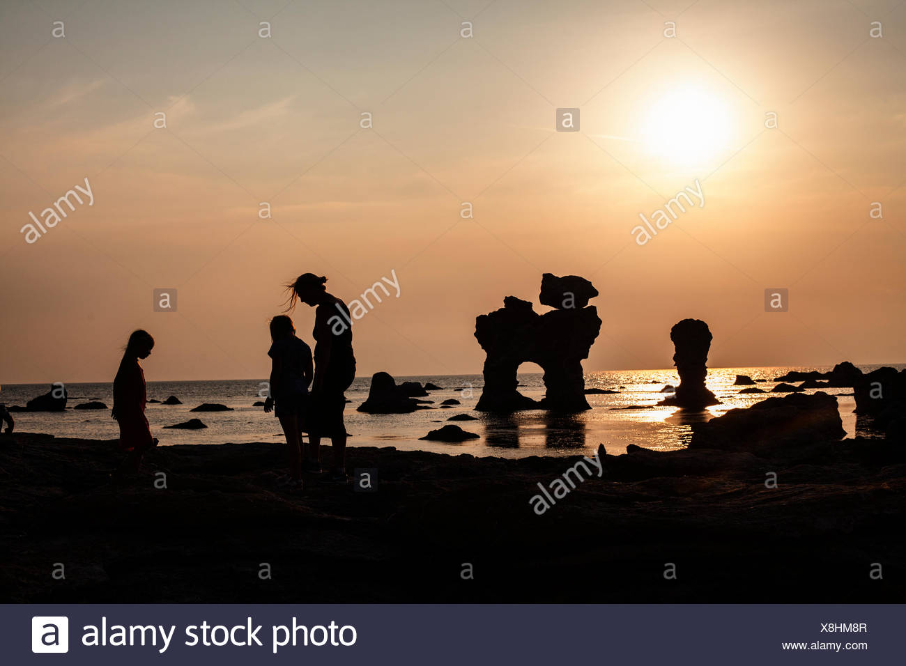 Sweden, Gotland, Faro, Gamle hamn, Silhouette of mother and children (8-9, 10-11) on beach at sunset Stock Photo