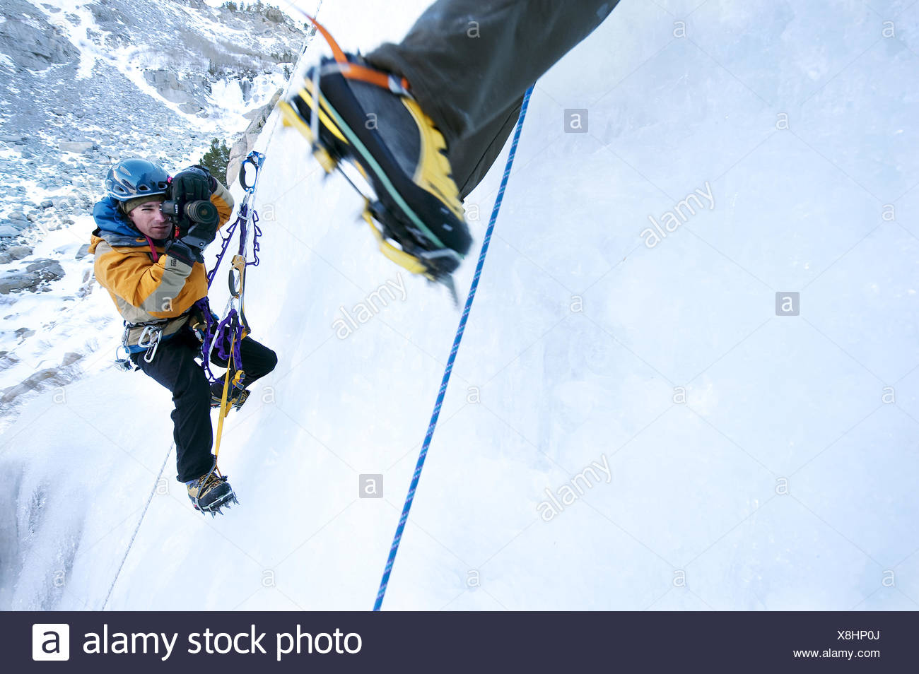 A photographer photographs an ice climber in Calif. - Stock Image