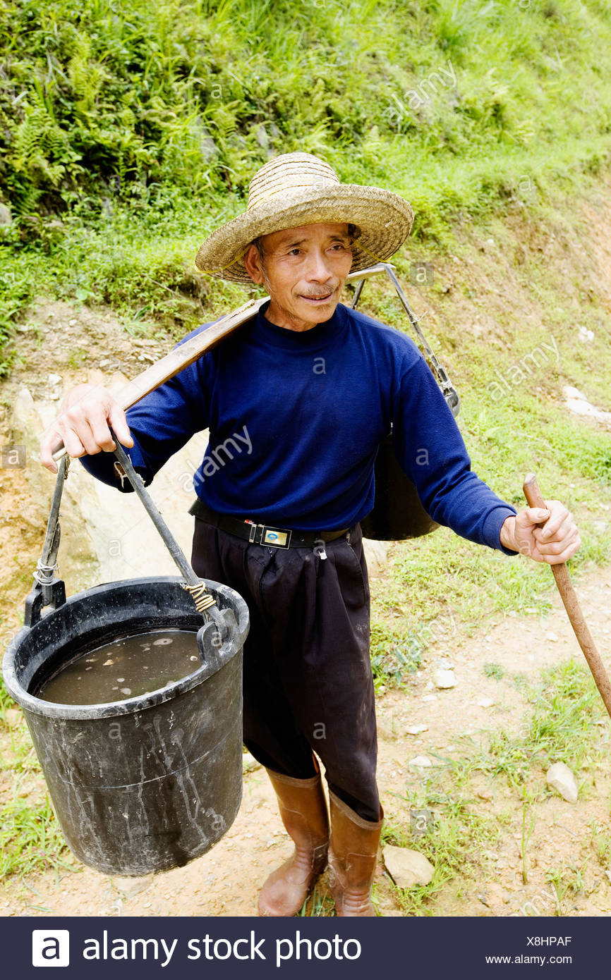 Senior man carrying a bucket full of water on his shoulder, Jinkeng Terraced Field, Guangxi Province, China - Stock Image