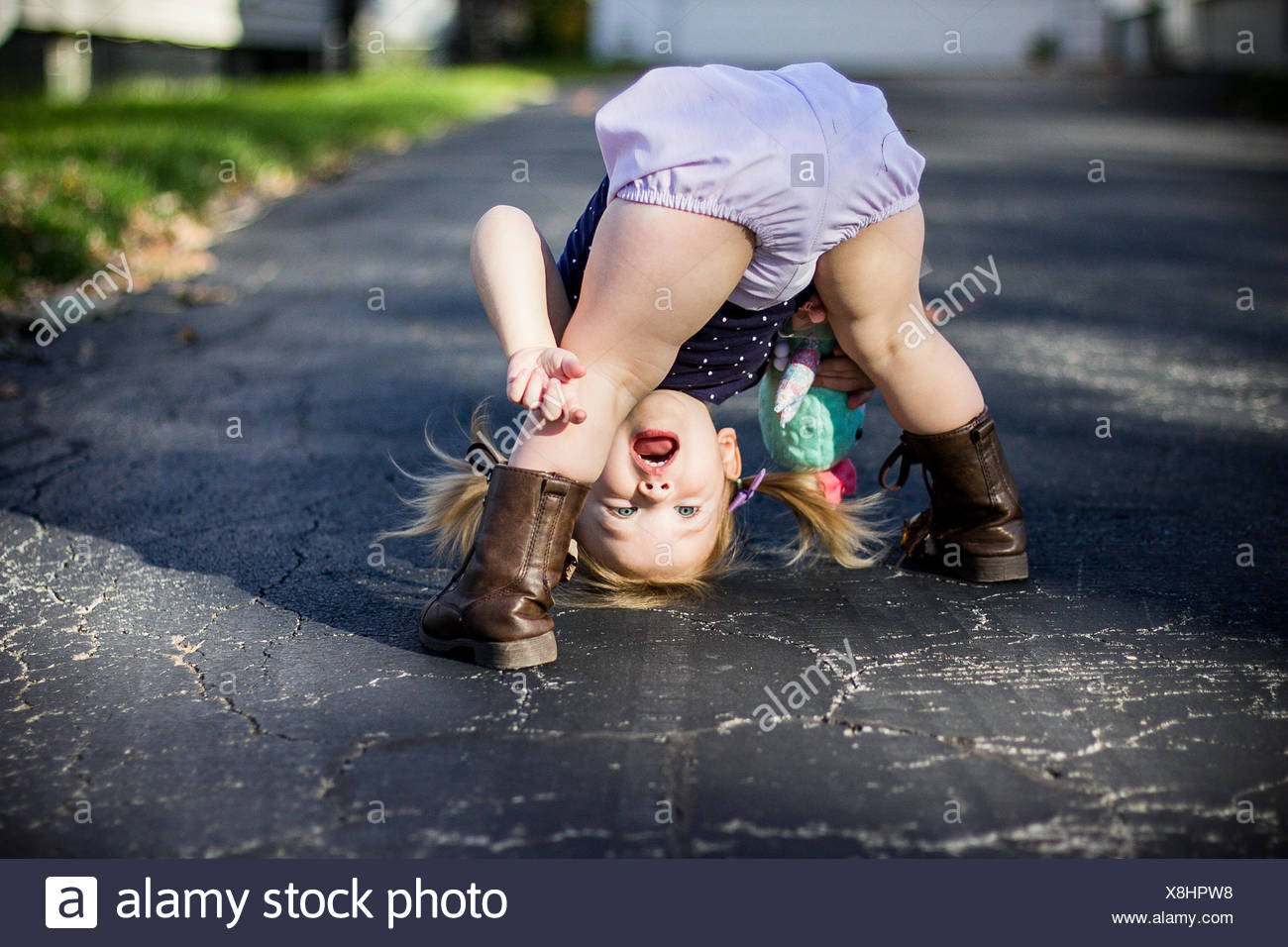 Girl bending over and looking through her legs upside down - Stock Image