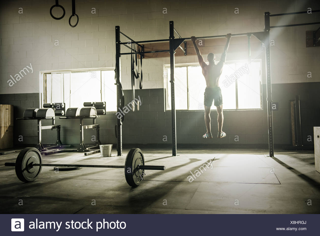 Young man training on exercise bar in gymnasium - Stock Image