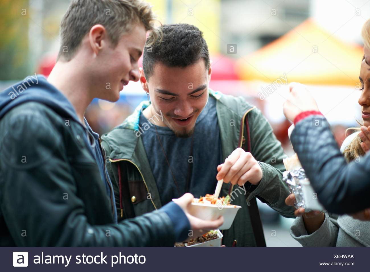 Group of young adults eating takeaway food, outdoors - Stock Image