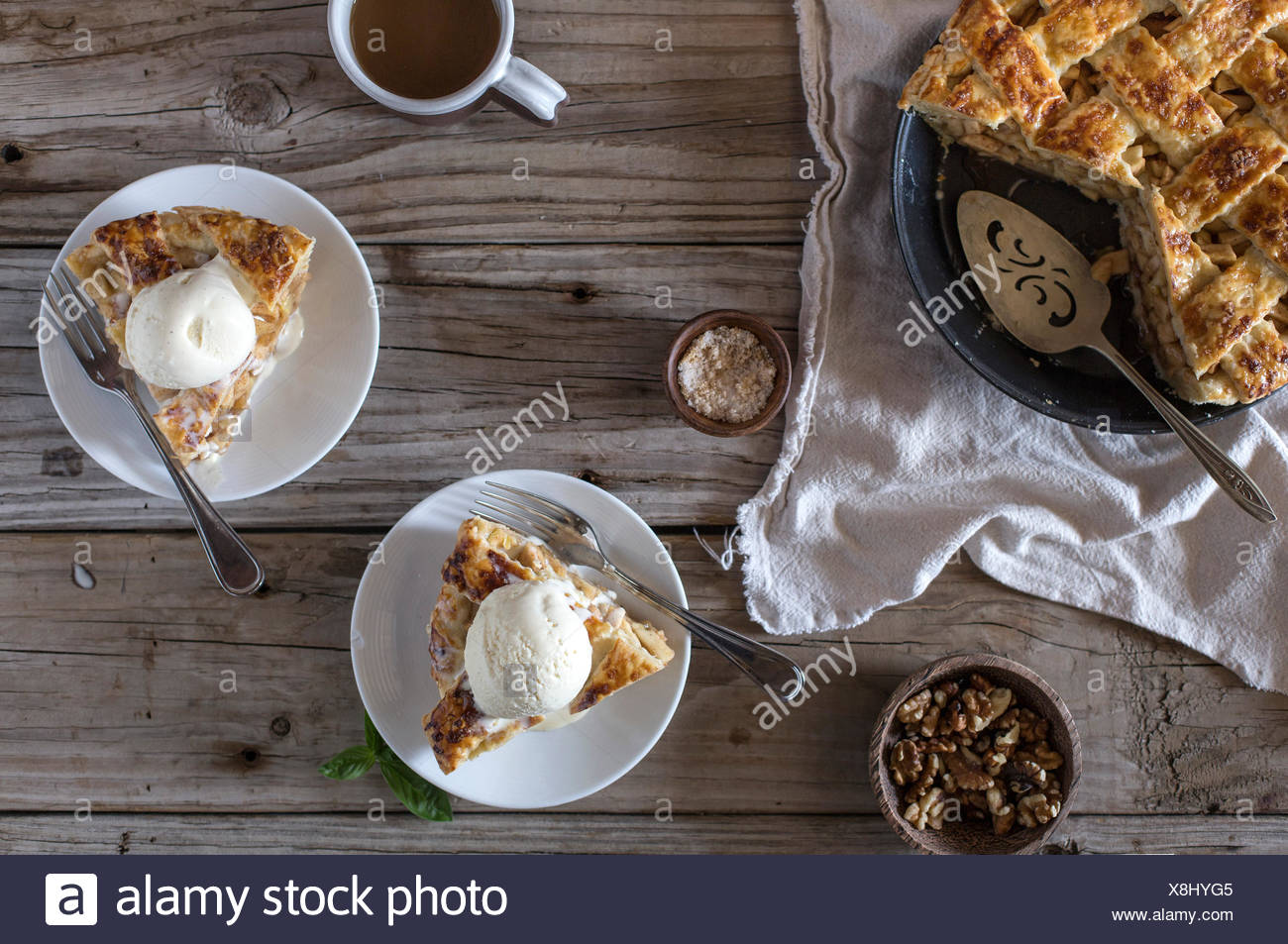 Two slices of a caramel apple pie (topped with vanilla ice cream) is displayed on a farm table. - Stock Image