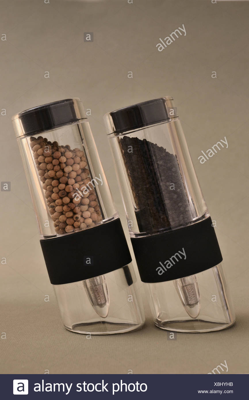 black salt (from Hawaii) and white pepper in salt and pepper mills - Stock Image