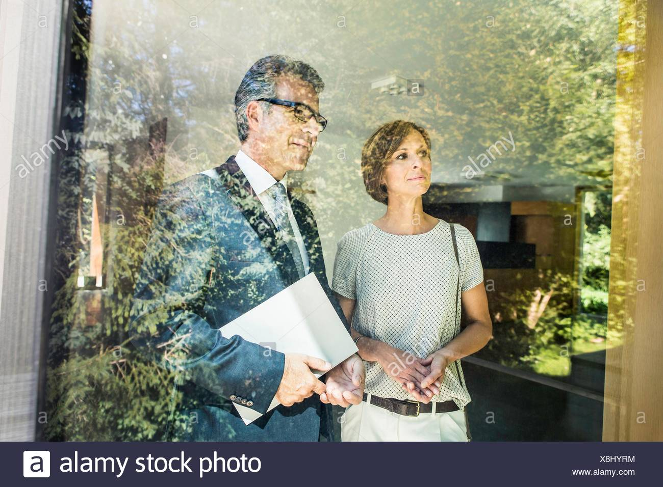 Mature woman looking at new house with estate agent Stock Photo