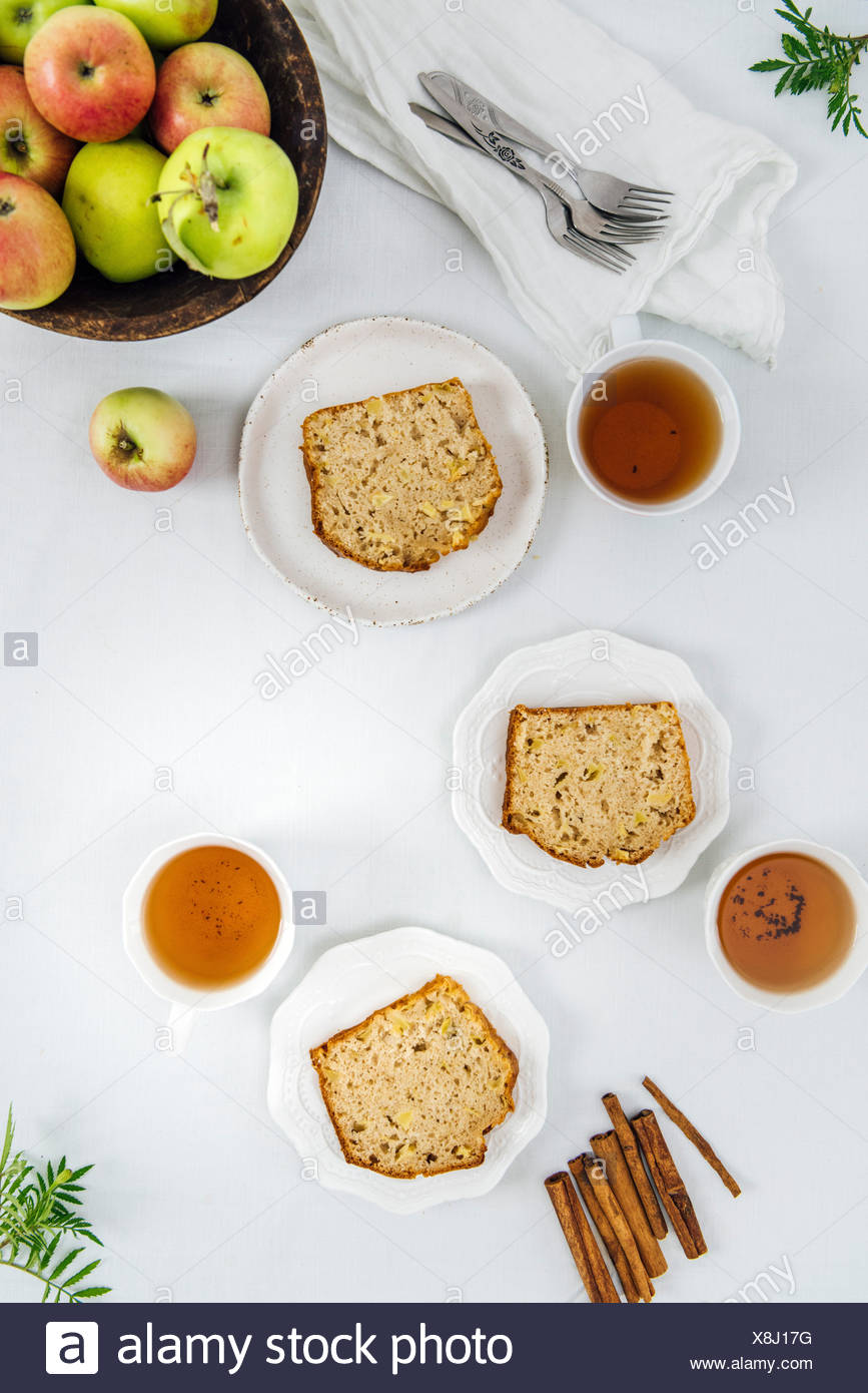 Cinnamon apple bread slices served on three white plates photographed from top view. Three cups of tea and apples in a wooden bowl accompany. - Stock Image
