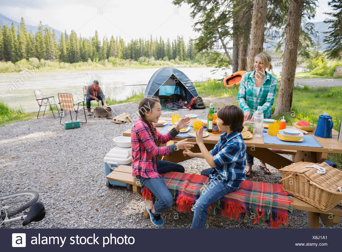 Family relaxing together at campsite - Stock Image