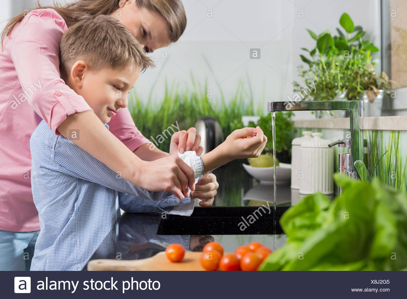 Mother assisting son in folding sleeves while washing hands in kitchen - Stock Image