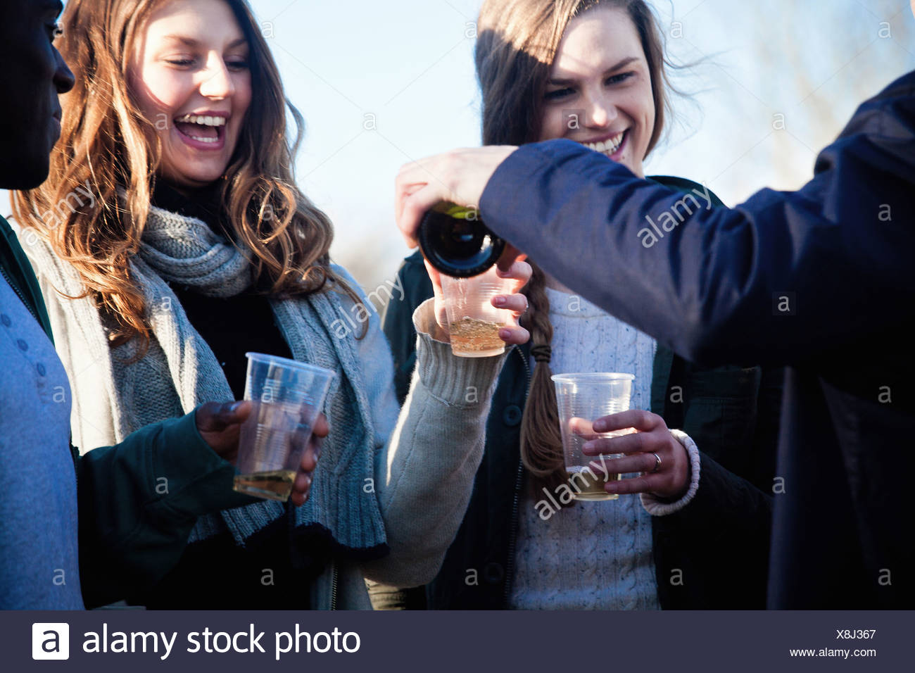 Young adult friends enjoying white wine outdoors - Stock Image