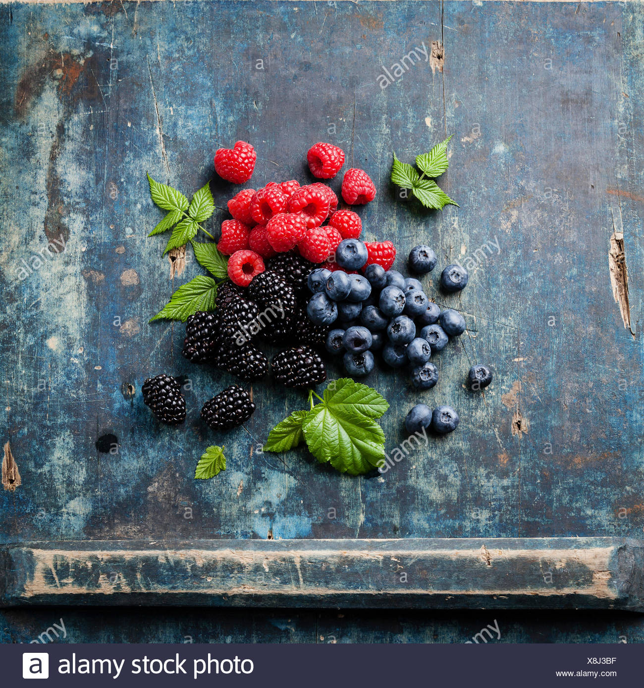 Mix of fresh berries with leaves on blue wooden background - Stock Image
