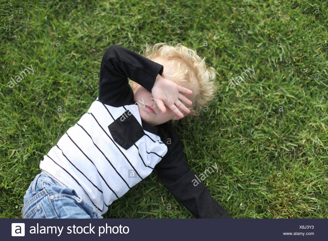Boy lying on the ground with hand covering face - Stock Image