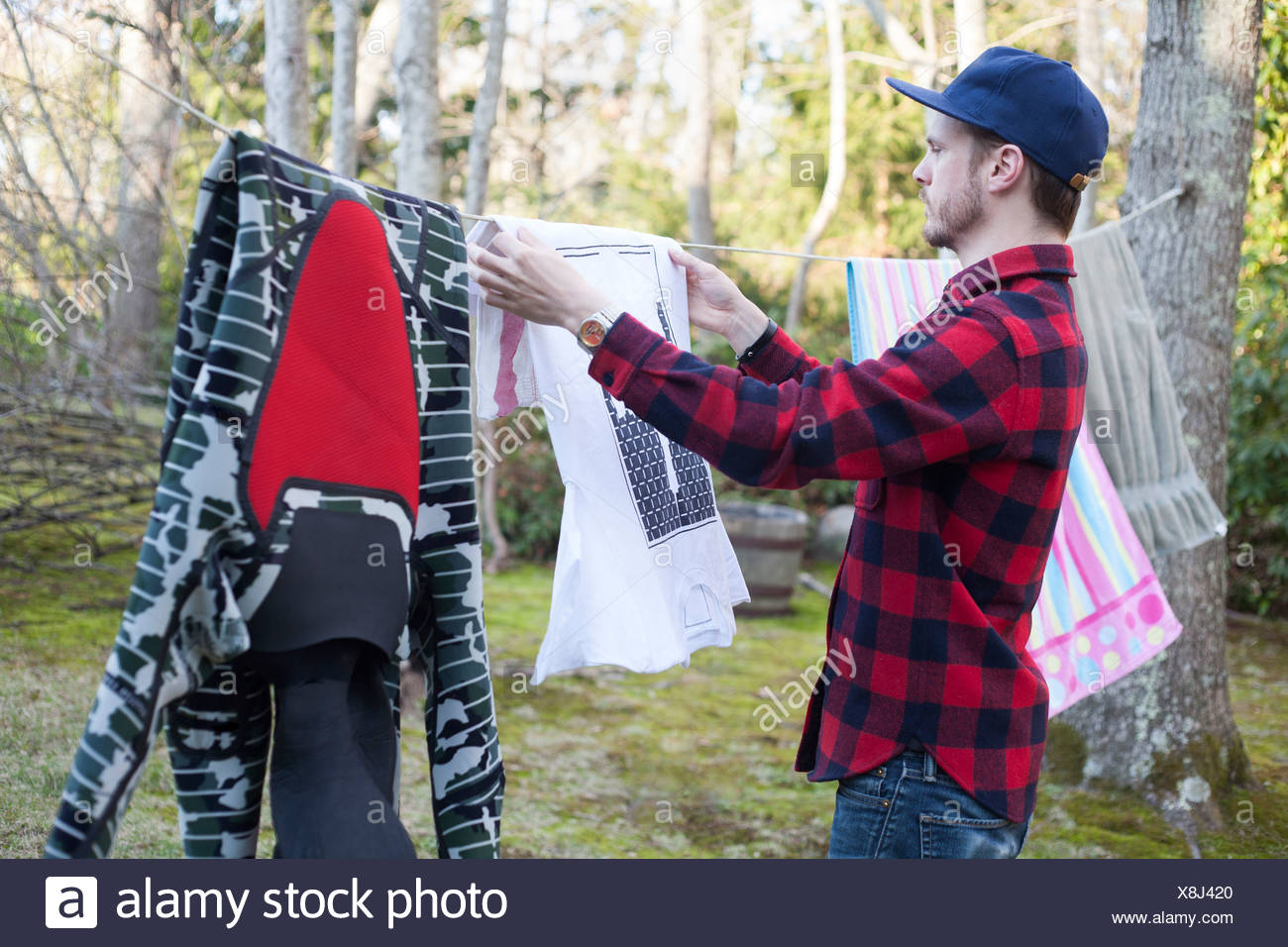 Mid adult man hanging out laundry in garden - Stock Image