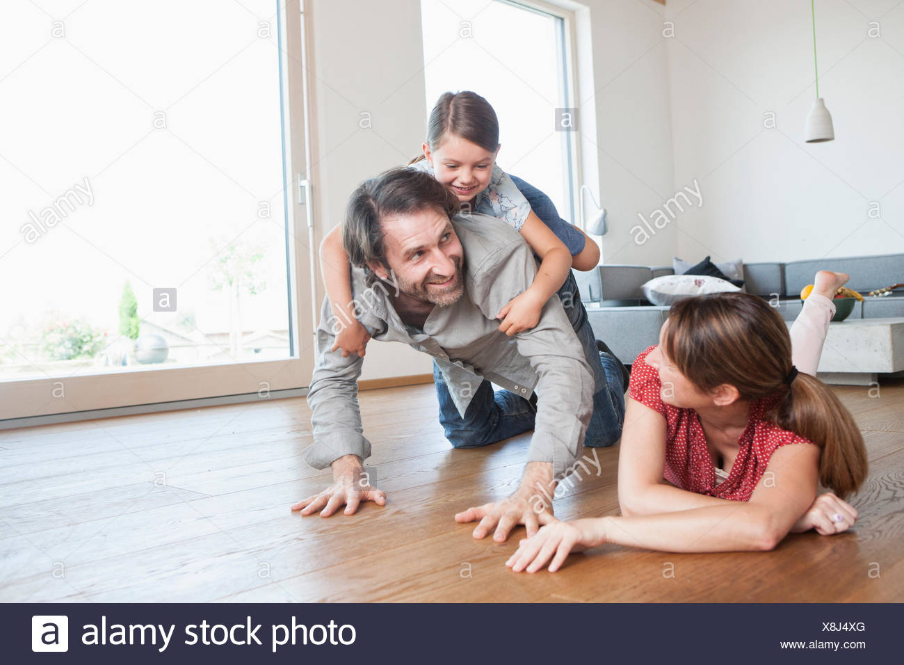 Happy family lying on floor, playing with daughter Stock Photo