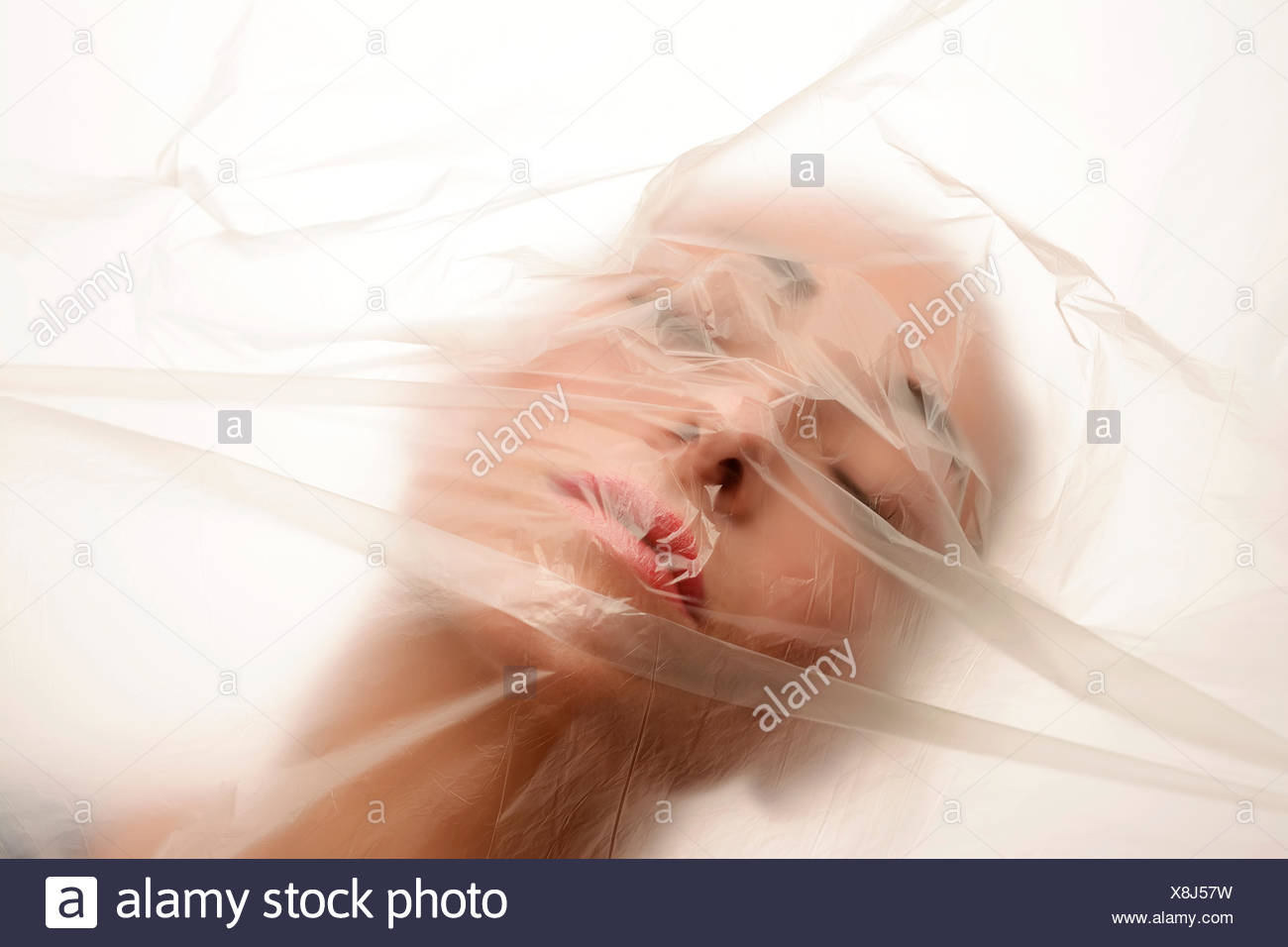 Face of young woman behind foil - Stock Image