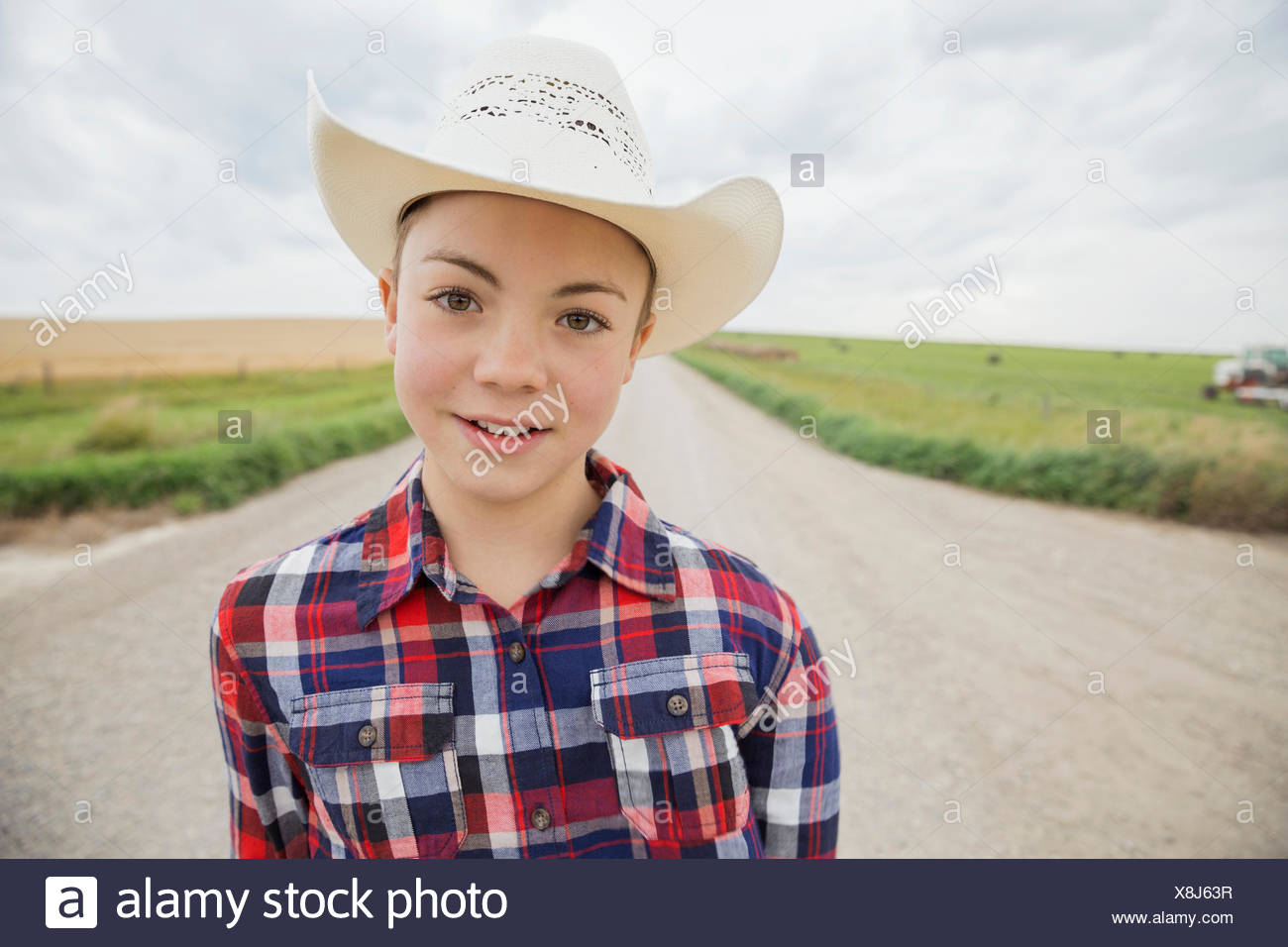 Portrait of boy in cowboy hat on road - Stock Image