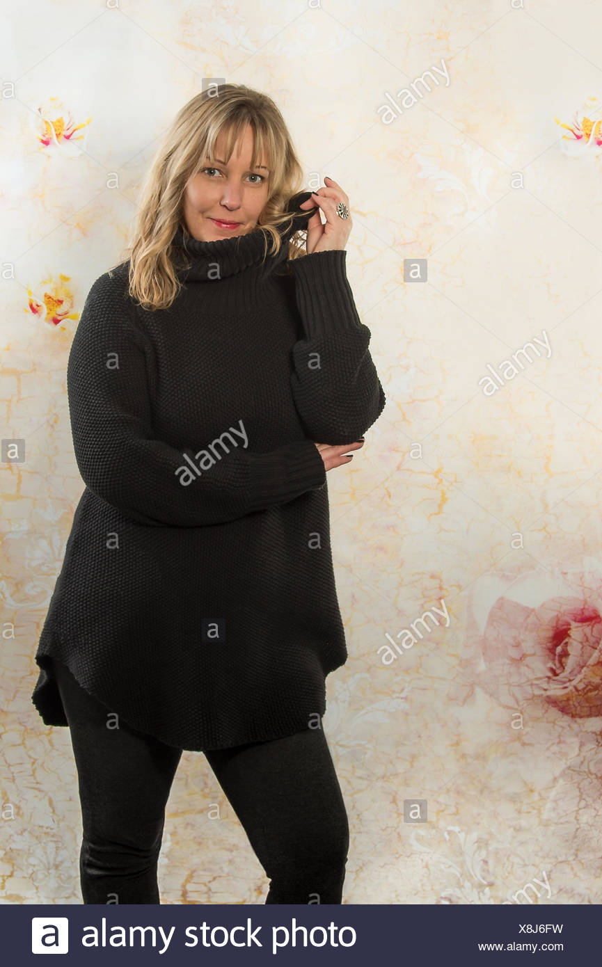blonde woman with a thick sweater - Stock Image