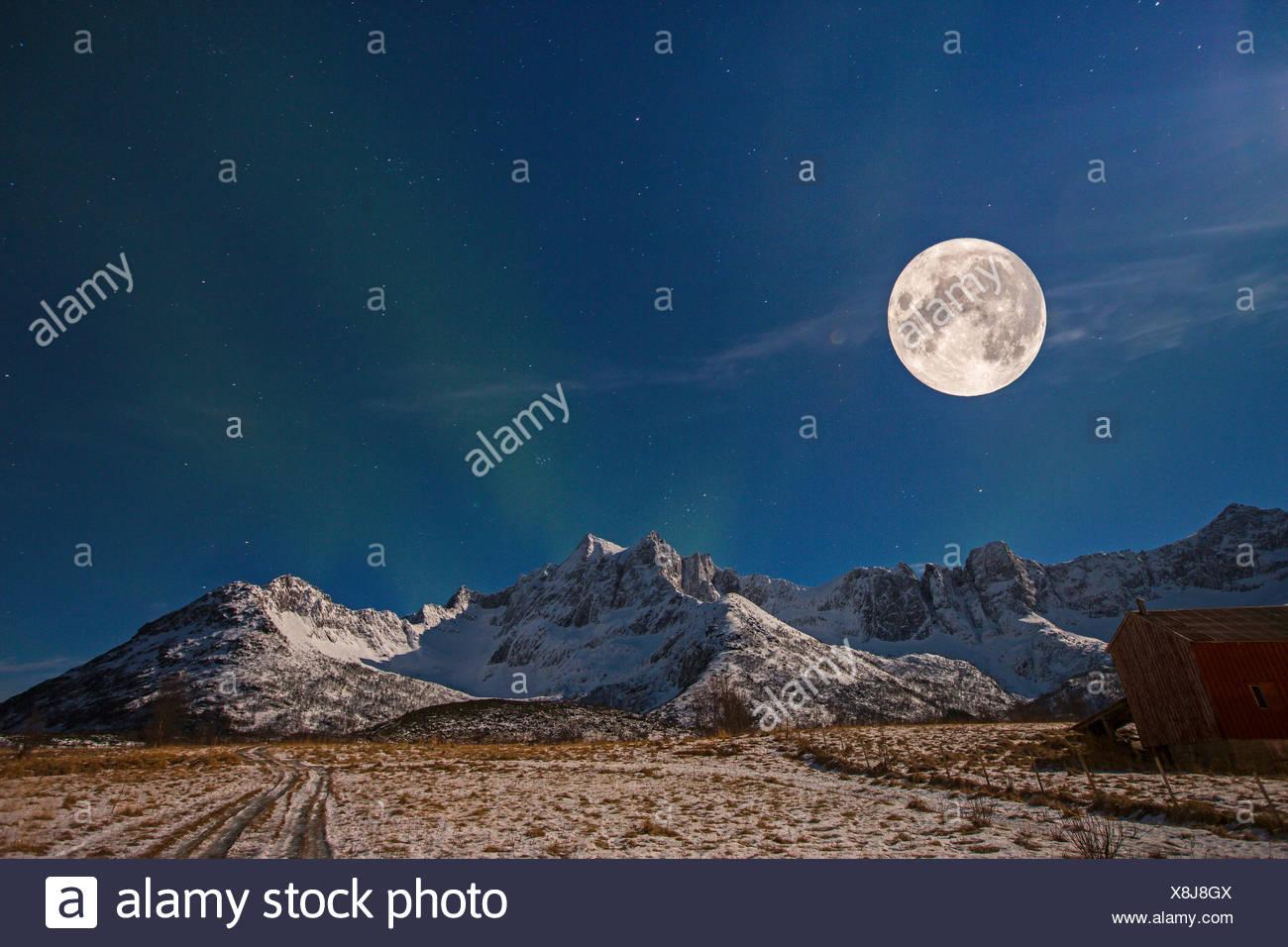 Vollmond mit Sternenhimmel und Nordlicht ueber Bergkette, Norwegen, Troms, Senja   full moon with starry sky and polar light ove - Stock Image