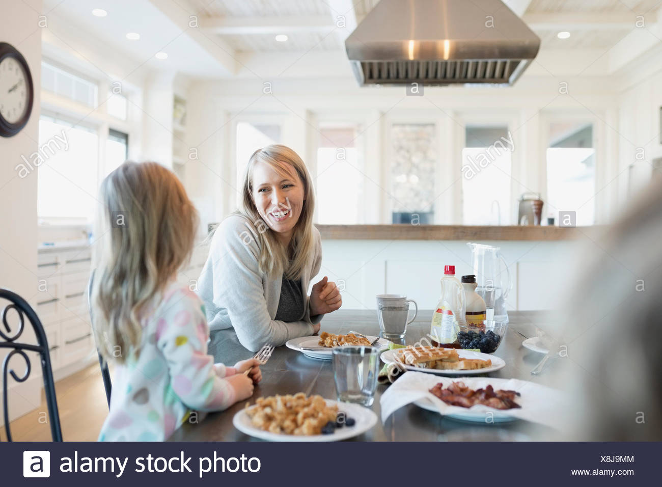 Mother and daughter eating waffles at breakfast table - Stock Image
