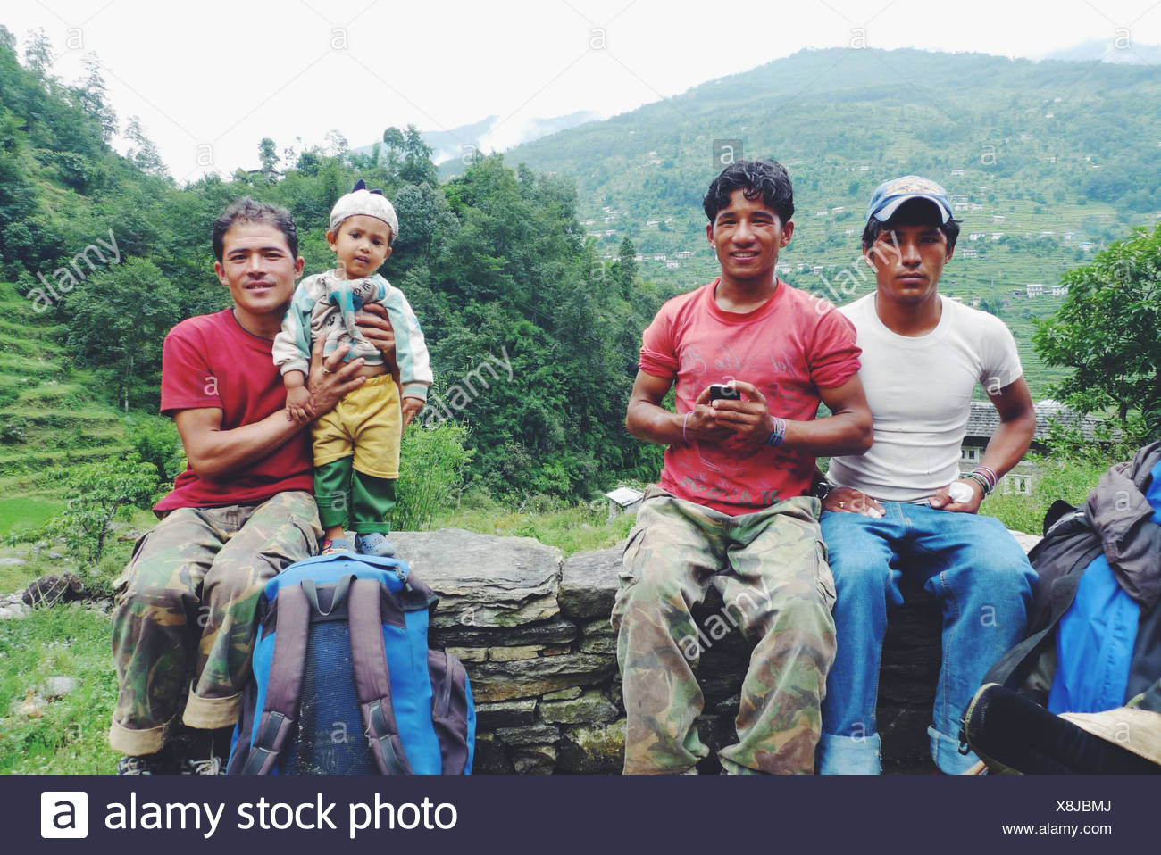 Three men sitting on a wall with a baby boy, Nepal - Stock Image