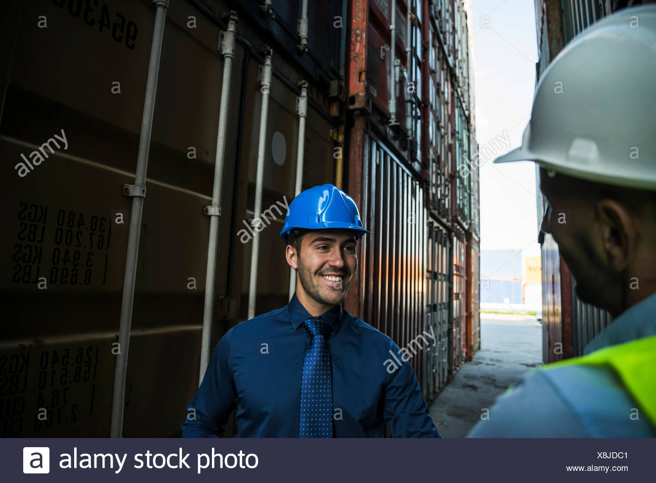 Two men with safety helmets at container port - Stock Image