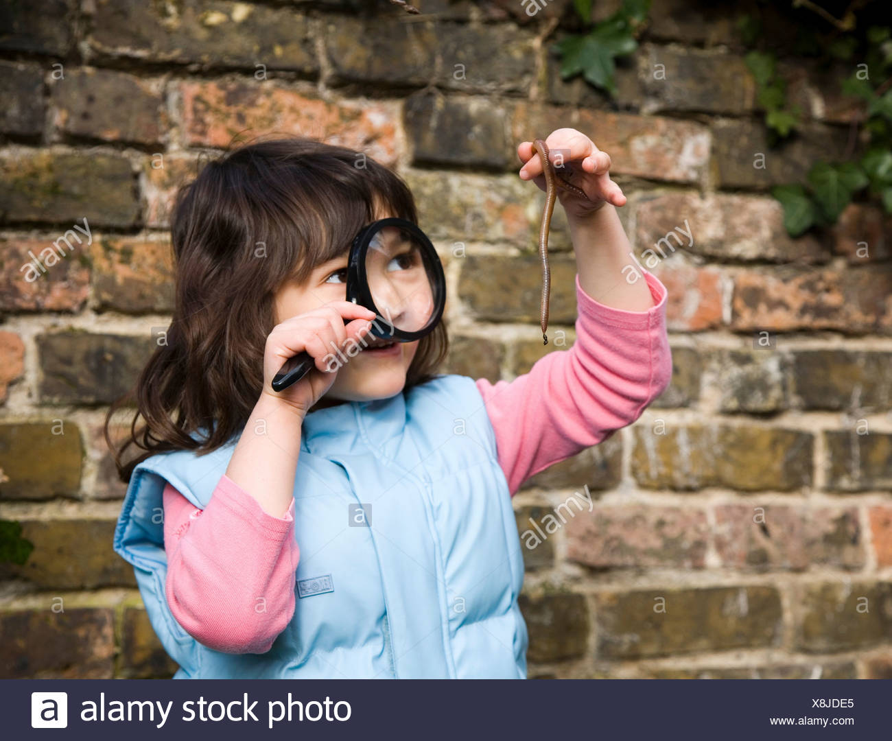 Girl looking at worm with magnifying glass - Stock Image