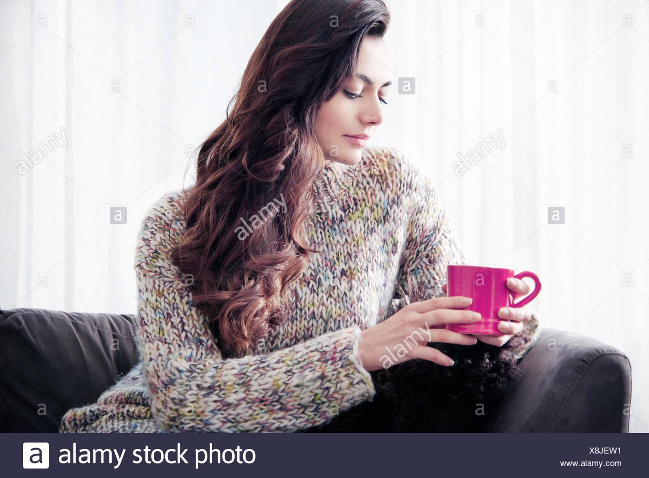 Woman drinking coffee on sofa - Stock Image