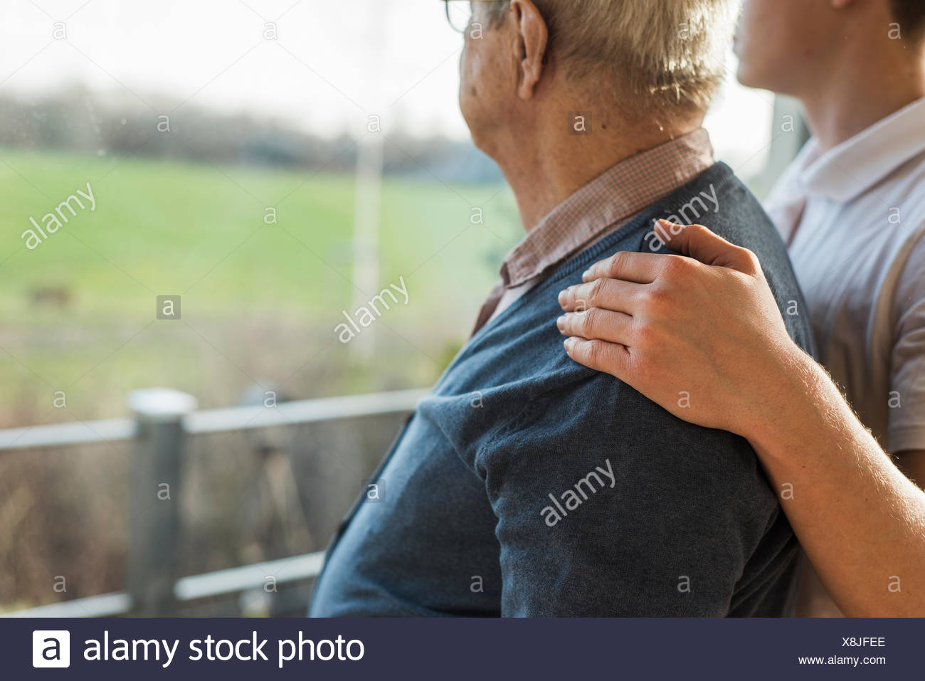 Young man's hand on the shoulder of a senior man - Stock Image