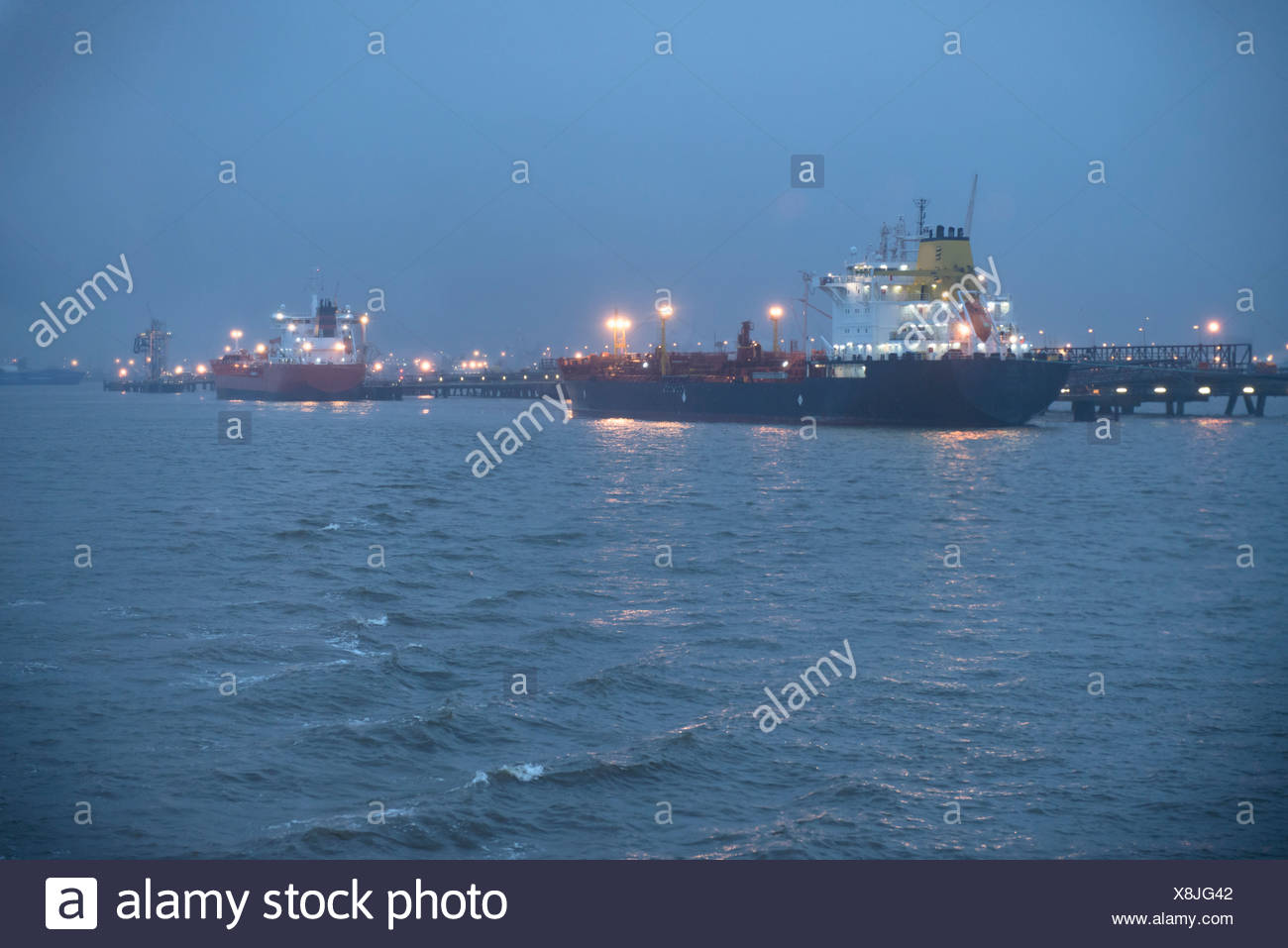 Tanker ships lit up at night - Stock Image