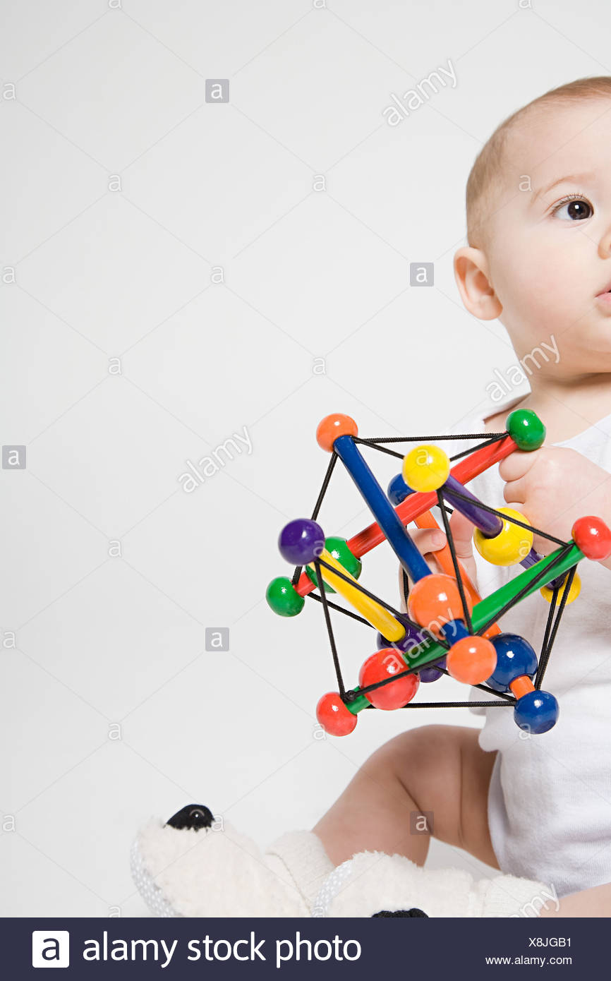 A baby holding a toy - Stock Image