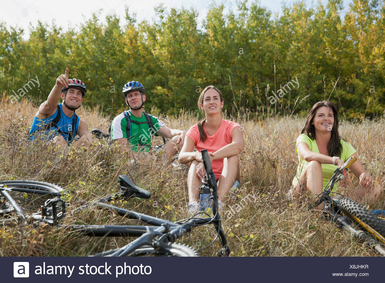 Four people relaxing in field with bikes. - Stock Image