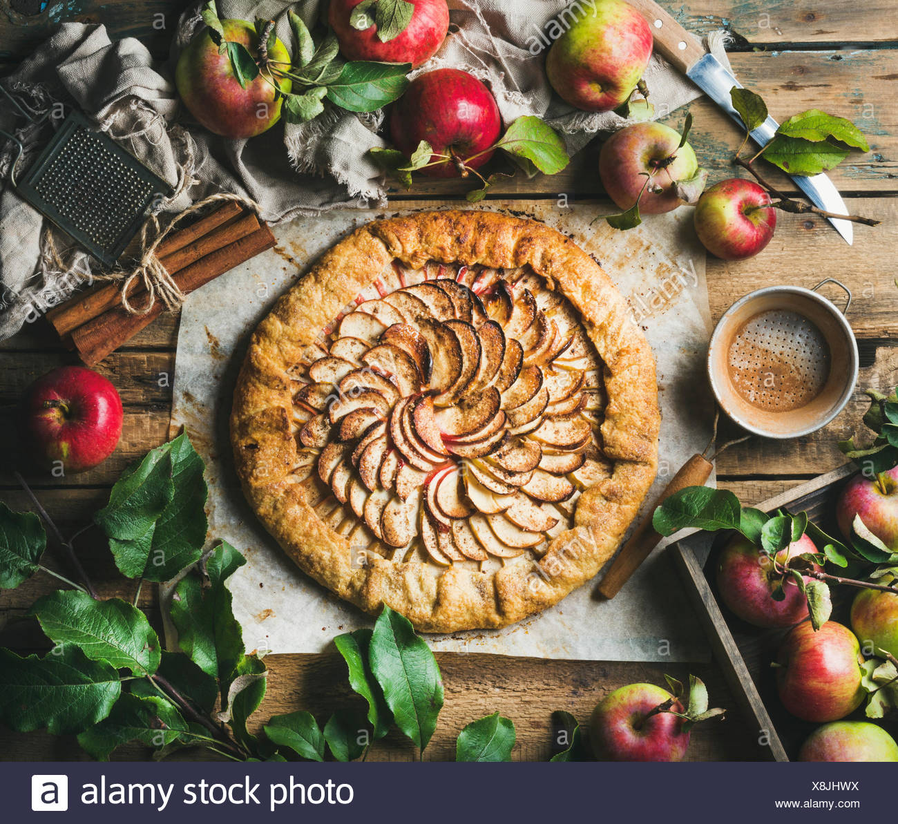 Apple crostata pie with cinnamon served with fresh garden apples with leaves on rustic wooden background, top view, horizontal c - Stock Image