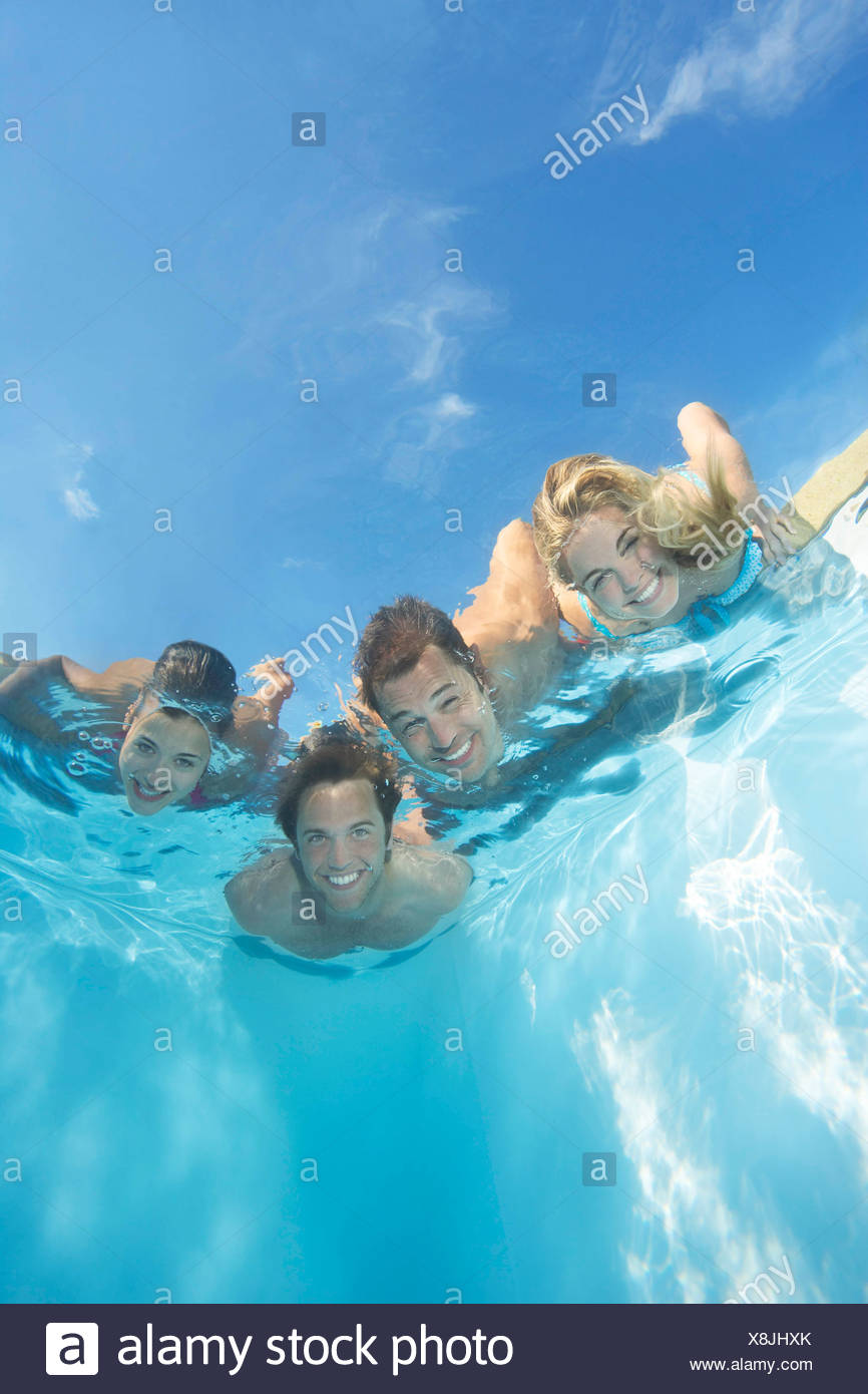 Group of friends submerged in pool - Stock Image