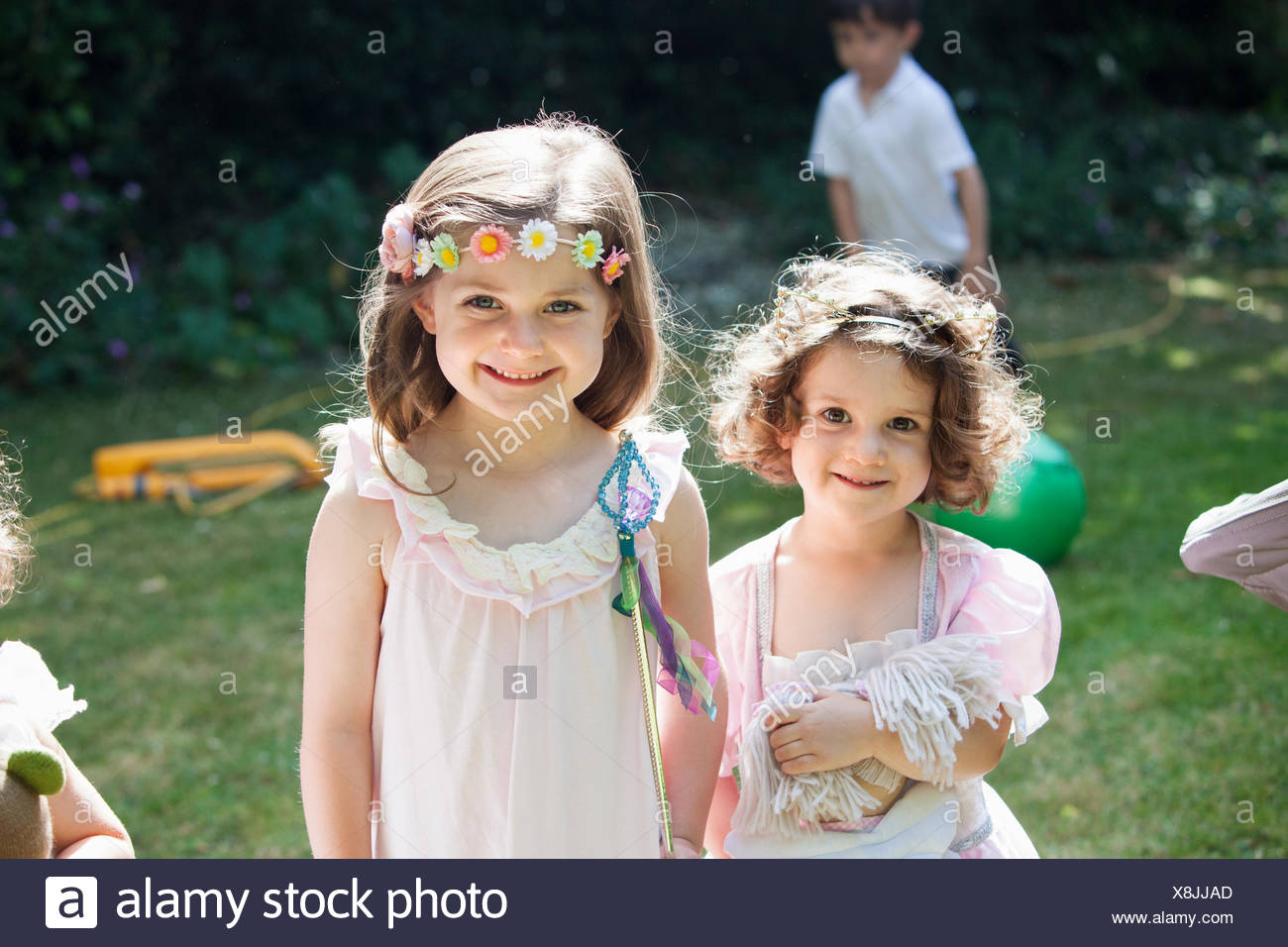 Two smiling young girls at a garden party. - Stock Image