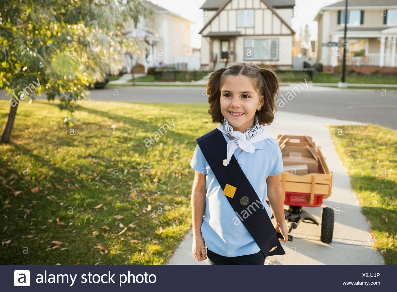 Smiling girl scout with wagon selling cookies neighborhood - Stock Image