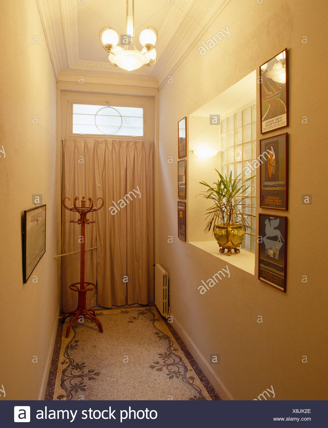 Mosaic tiled floor and recessed glass brick window in narrow hall with cream curtain on door - Stock Image