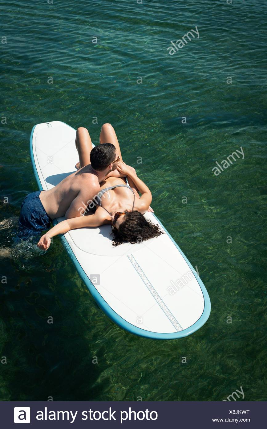 Overhead view of romantic young couple on paddleboard at sea - Stock Image