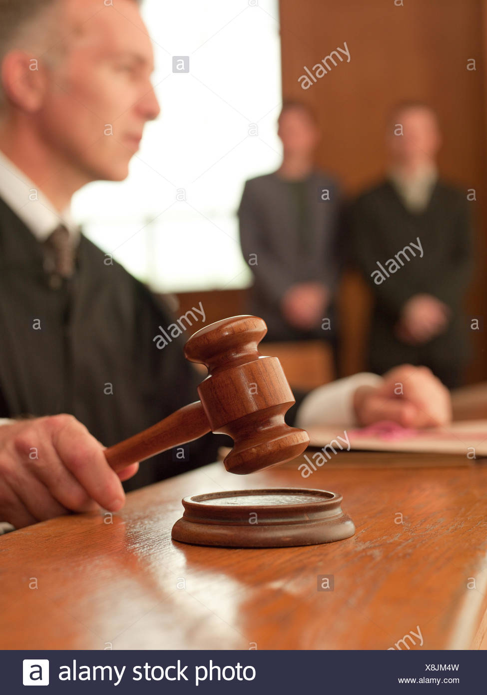 Judge holding gavel in courtroom - Stock Image