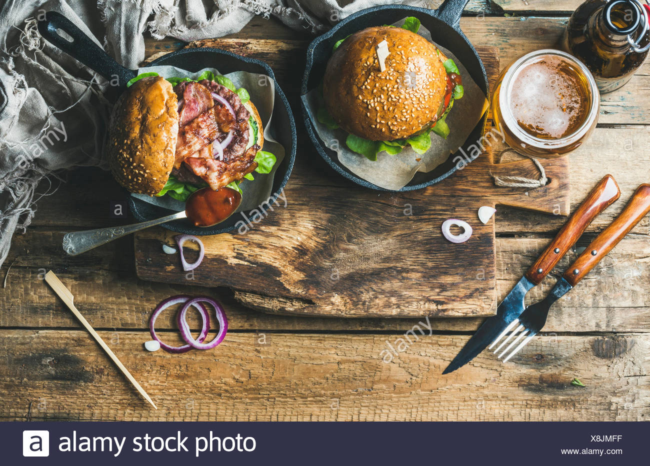 Homemade beef burgers with crispy bacon and vegetables in small pans and glass of wheat beer on rustic serving board over shabby - Stock Image