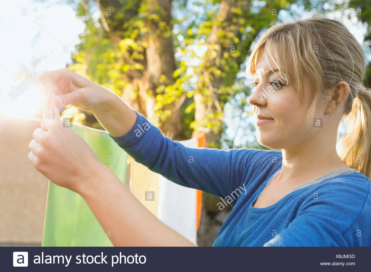 Woman hanging clothing on clothesline in backyard - Stock Image