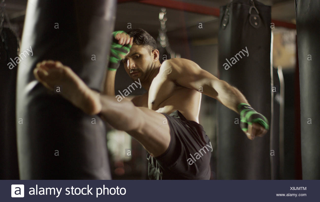 Selective focus view of man kickboxing punching bag in gym - Stock Image