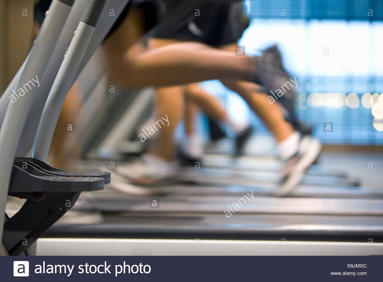 Legs running on treadmills in health club - Stock Image