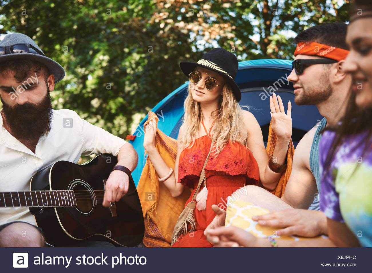 Young adult friends playing acoustic guitar while festival camping - Stock Image