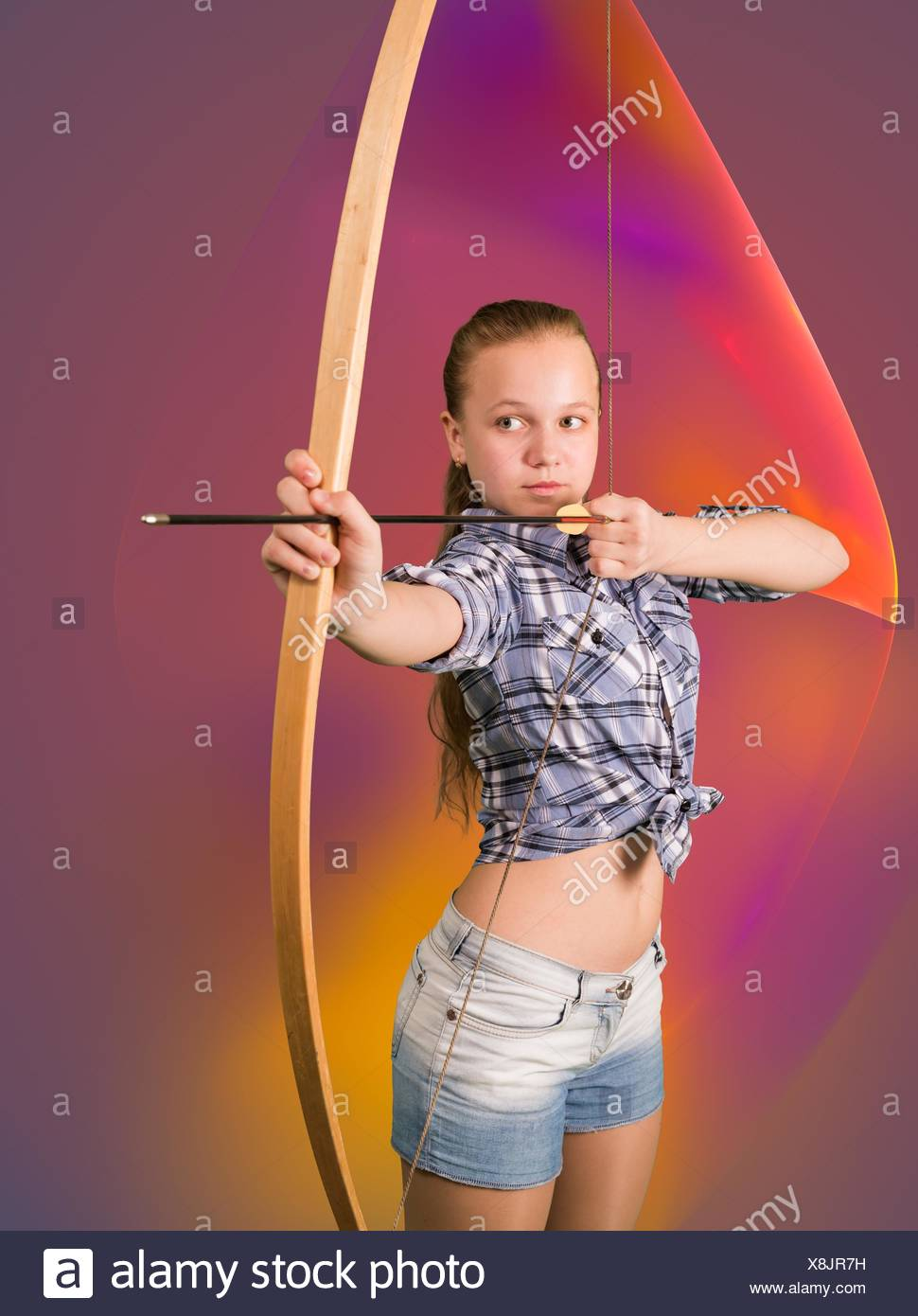 Teen girl practicing archery standing on abstract background. - Stock Image