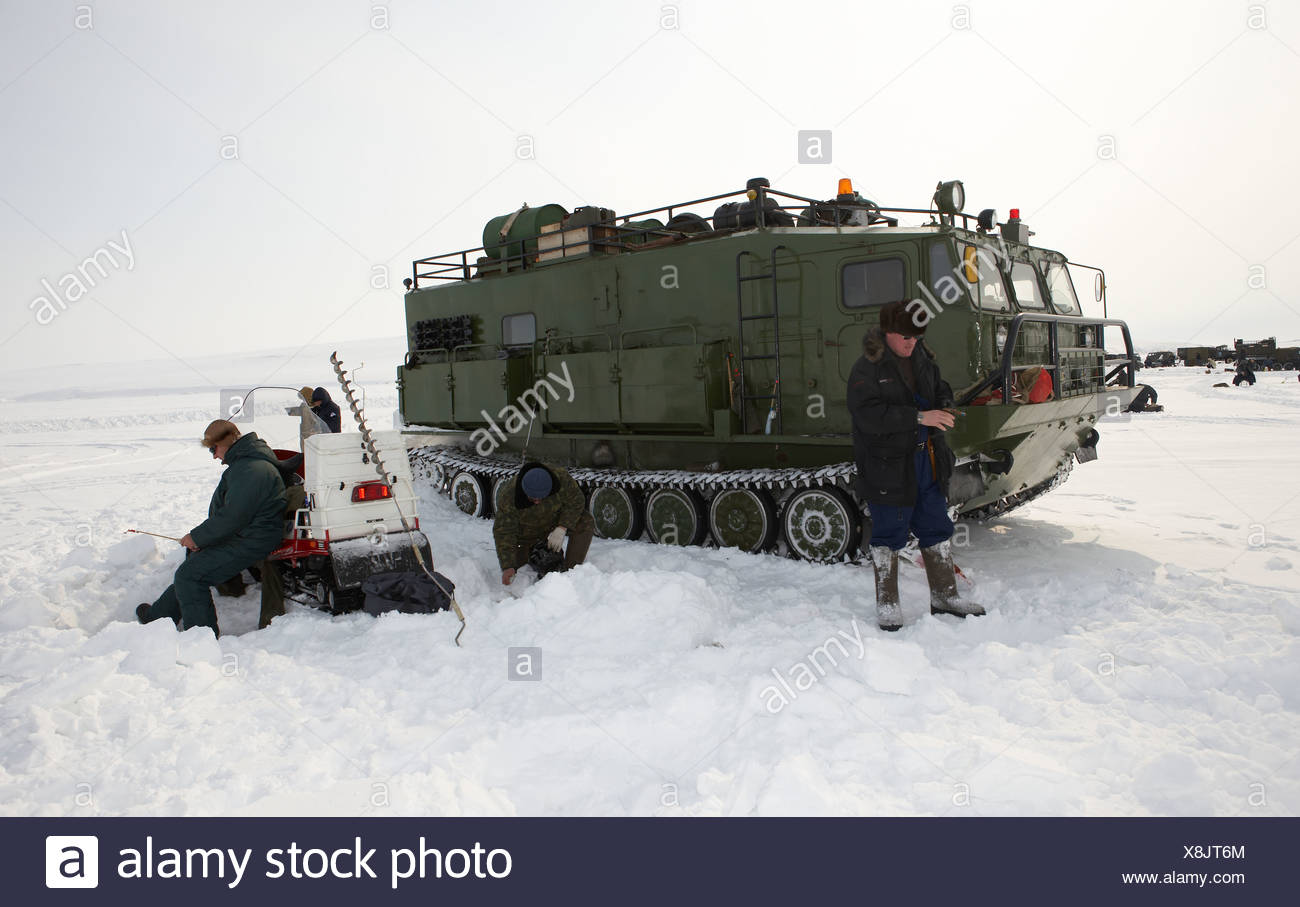 Ice fishing for smelts in front of modified tank, (Vezdekhod) Anadyr Chukotka, Siberia Russia - Stock Image