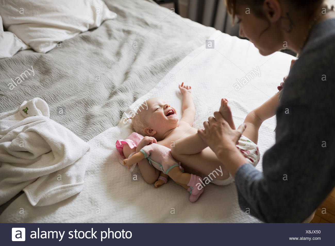 Mother changing baby daughter - Stock Image