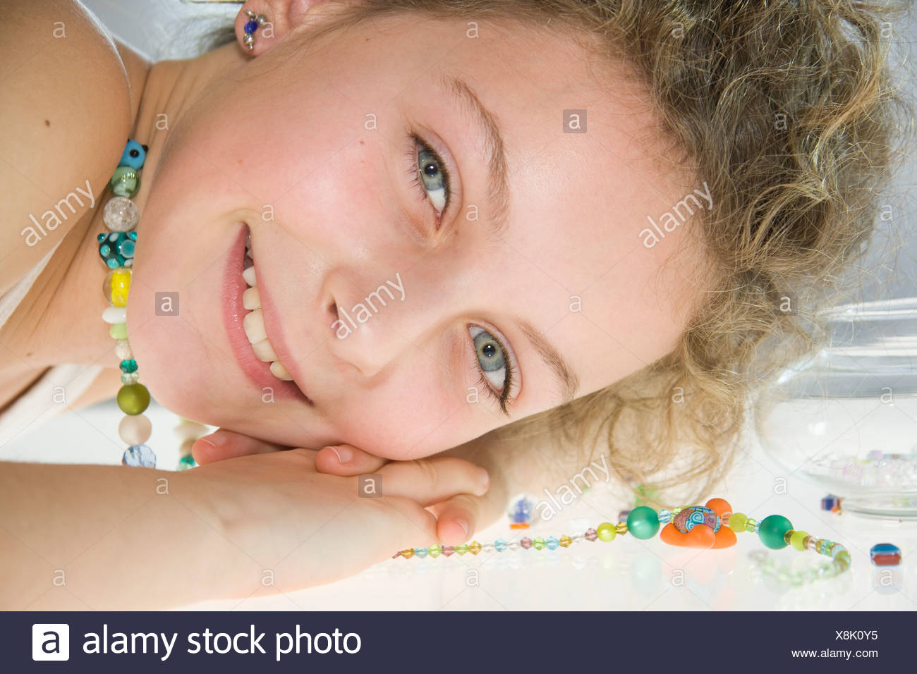 A young girl wearing a handmade bead necklace, face resting on a table - Stock Image